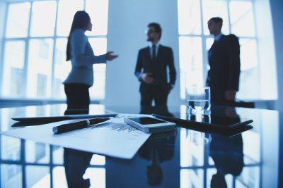 Image of business document and electronic devices at workplace with group of business people talking on background